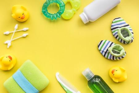 Foto de Bath cosmetic set for kids, towel and toys on yellow background top view space for text - Imagen libre de derechos