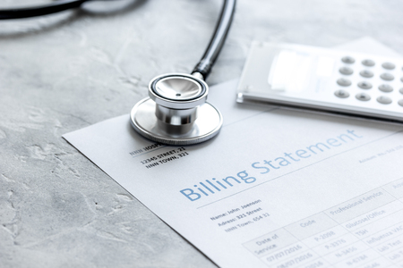 Foto de stethoscope, billing statement for doctors work in medical center stone background - Imagen libre de derechos