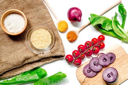 Foto de cooking paella with vegetables and rice ingredients on white kitchen desk background top view - Imagen libre de derechos