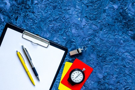 Foto de Set to judge competition. Yellow and red cards, stopwatch, whistle, pad, pen on blue table background top view. - Imagen libre de derechos