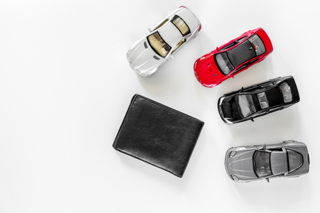 Photo pour Buying car. Toy cars and wallet on white background top view. - image libre de droit
