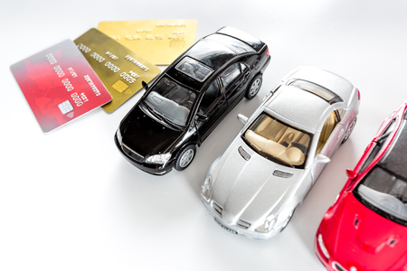 Photo pour Choosing car concept. Toy cars and bank card on white background top view copyspace. - image libre de droit