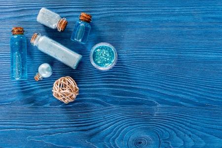 Photo pour Spa set with sea salt, blue clay and lotion on blue wooden table background top view copyspace - image libre de droit
