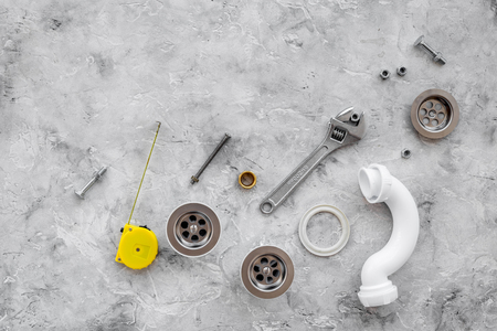 Photo pour Drain parts and plumbing tools on grey stone background top view. - image libre de droit