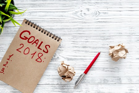 Photo for Make a goals list for 2018. Notebook, pen and wrinkled sheets of paper background top view. - Royalty Free Image