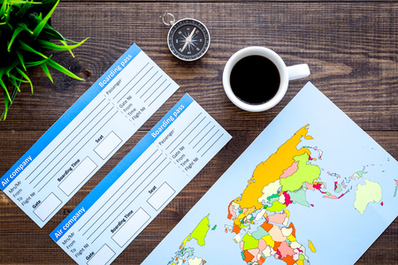 Photo pour Accessories for traveling with tickets, map and cup of coffee on office desk dark wooden background top view - image libre de droit