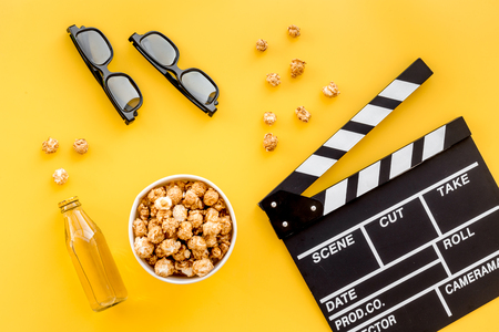 Photo pour Snacks for film watching. Popcorn and soda near clapperboard, glasses on yellow background top view. - image libre de droit