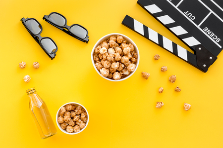 Photo for Snacks for film watching. Popcorn and soda near clapperboard, glasses on yellow background top view. - Royalty Free Image