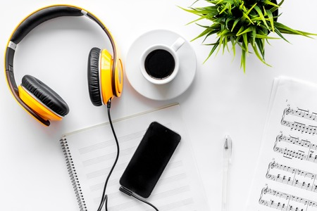 Foto de Desk of musician for songwriter work set with headphones and smartphone on white background top view mockup - Imagen libre de derechos