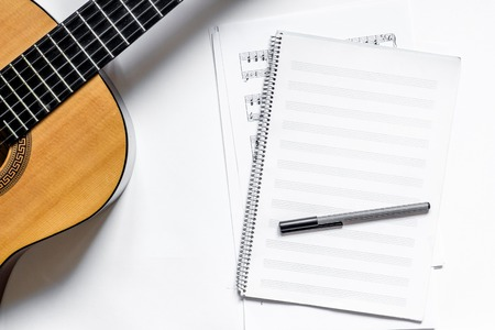 Foto de musician work set with blank paper for notes and guitar white table background top view space for text - Imagen libre de derechos