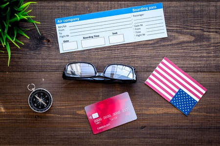 Photo pour accessories for treveling with tickets, flags and credit card on office desk dark wooden background top view - image libre de droit