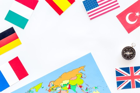 Photo pour planing trip with compass, flags and world map on white table background top view space for text - image libre de droit