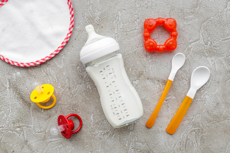 Photo for preparation of mixture baby feeding with infant formula powdered milk in bottle, spoon and toys on gray stone background top view - Royalty Free Image