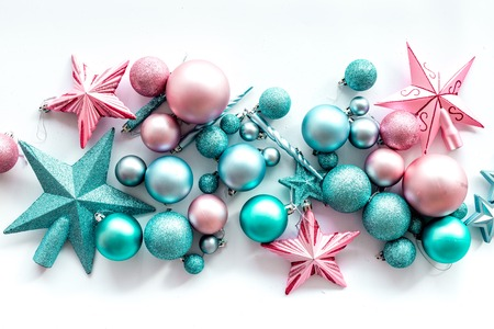 Foto de Christmas decoration concept. Pink and blue stars and balls near pine branches on white background top view. - Imagen libre de derechos