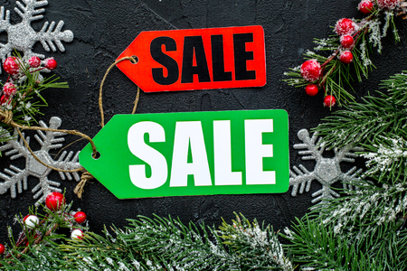 Foto de Winter sale. Sale labels near spruce branches on black background top view. - Imagen libre de derechos