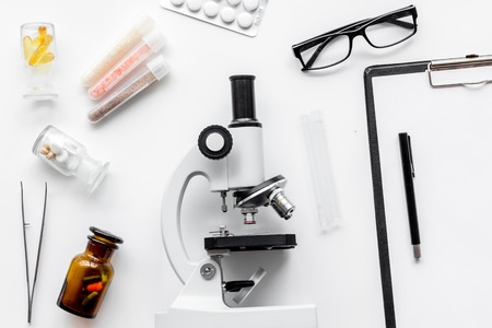 Foto de Do medcal tests. Microscope, tablet, pills and test tube on white background top view. - Imagen libre de derechos