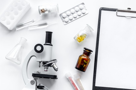 Foto de Microscope, pills and tablet on white background top view. - Imagen libre de derechos