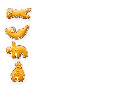 Foto de Gingerbread cookies in shape of yoga asanas on white background top view copyspace - Imagen libre de derechos