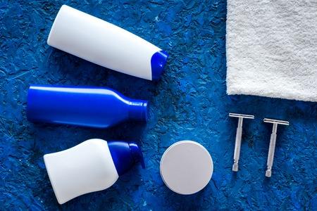 Photo pour Mens cosmetics for hair care and shaving. Shampoo, gel, razor, wax on blue background top view copyspace - image libre de droit