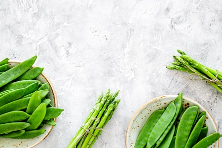 Photo pour Healthy vegetarian food. Asparagus and pea on grey stone background top view. - image libre de droit