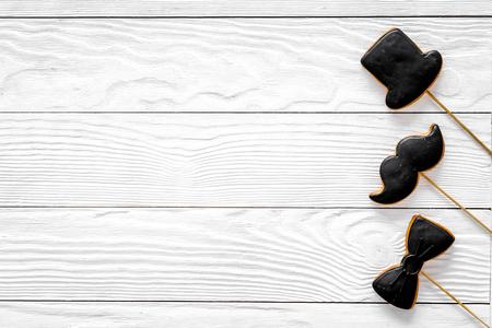 Foto de Men birthday concept. Set of cookies in shape of black tie, mustache and hat. White wooden background top view copyspace - Imagen libre de derechos