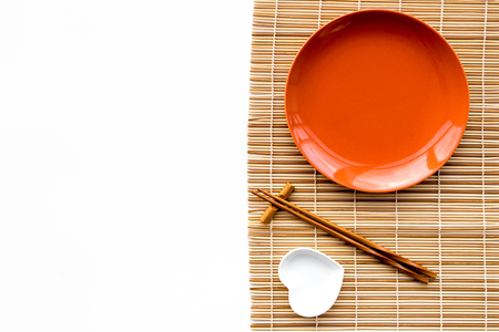 Photo pour Table setting for sushi roll. Empty plate on mat near chopstick and bowl for sause on white background top view copyspace - image libre de droit