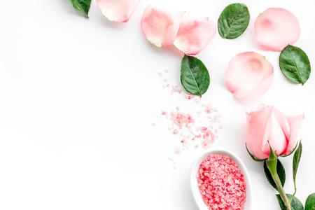 Photo pour Pattern with rose oil cosmetics. Rose petals, spa salt on white background top view. - image libre de droit