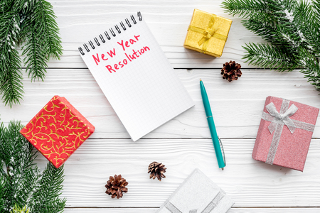 Foto de New year resolution. Notebook among gift boxes and spruce branch on white wooden background top view. - Imagen libre de derechos
