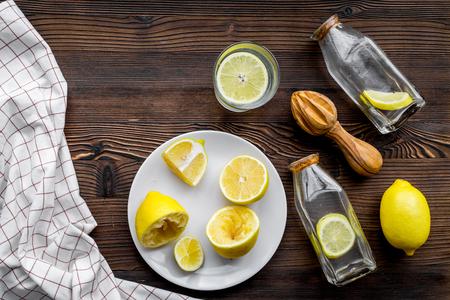 Foto de Fresh homemade lemonade. Lemons, juicer, glass for beverage on dark wooden background top view copyspace - Imagen libre de derechos