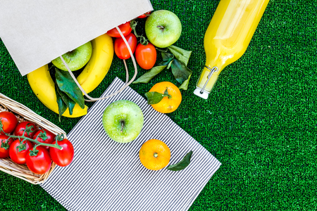 Photo for Fruits for picnic. Apple, banana, tangerine on green grass background top view copyspace - Royalty Free Image