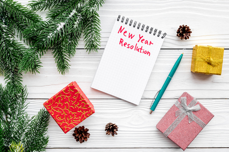 Photo pour New year resolution. Notebook among gift boxes and spruce branch on white wooden background top view - image libre de droit