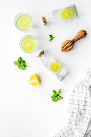 Foto de Prepare refreshing beverage lemonade. Lemons, juicer, bottle on white background top view copyspace - Imagen libre de derechos
