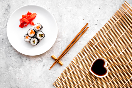 Foto de Sushi roll with salmon and avocado on plate with soy sauce, chopstick, wasabi on mat on grey stone background top view - Imagen libre de derechos