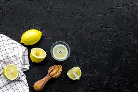 Foto de Make lemonade at home. Lemons, wooden juicer, glass for beverage on black background top view copyspace - Imagen libre de derechos