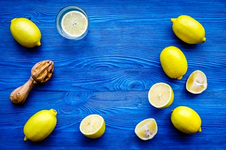 Photo pour Prepare refreshing beverage lemonade. Lemons, juicer on blue wooden background top view copyspace - image libre de droit