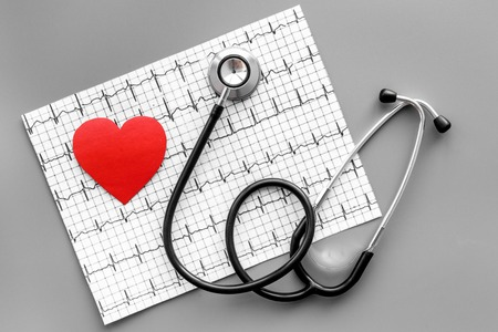 Foto de Examine the heart to prevent heart disease. Heart sign, cardiogram, stethoscope on grey background top view - Imagen libre de derechos