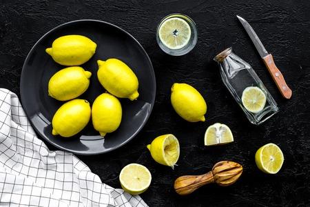 Foto de Make lemonade at home. Lemons, juicer, glass and bottle for beverage on black background top view - Imagen libre de derechos