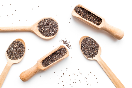 Photo pour Superfood chia seeds in a wooden spoon and scoop on white background top view - image libre de droit