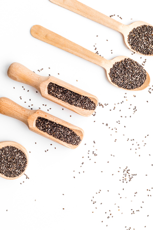 Photo pour Superfood chia seeds in a wooden spoon and scoop on white background top view copyspace - image libre de droit