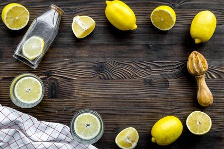Foto de Prepare refreshing beverage lemonade. Lemons, juicer, bottle on dark wooden background top view copyspace - Imagen libre de derechos