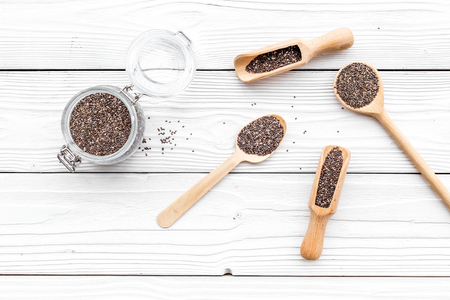 Photo pour Superfood chia seeds in a wooden spoon and scoop on white wooden background top view - image libre de droit