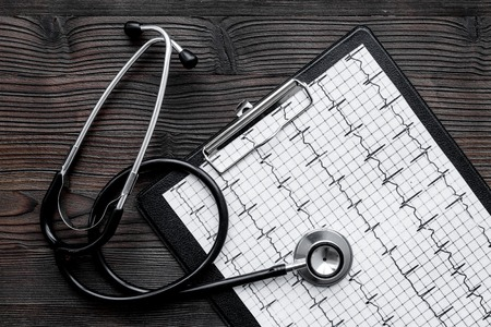 Foto de To diagnose heart disease. Cardiogram, stethoscope on white background top view - Imagen libre de derechos