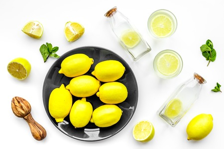 Foto de Fresh homemade lemonade. Lemons, juicer, glass for beverage on white background top view - Imagen libre de derechos