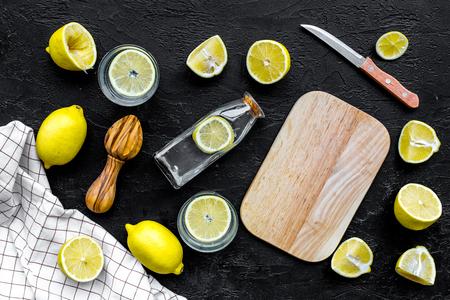 Foto de Make lemonade at home. Lemons, juicer, glass and bottle for beverage, knife, cutting board on black background top view - Imagen libre de derechos