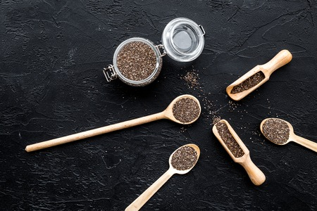 Photo pour Superfood chia seeds in a wooden spoon and scoop on black background top view. - image libre de droit