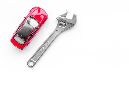 Photo pour Car repair concept. Wrench near car toys on white background top view. - image libre de droit