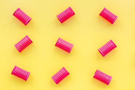 Photo pour Red curlers for hairdress. Pattern on yellow pastel background top view - image libre de droit