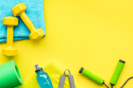 Photo pour Fitness background. Equipment for gym and home. Jump rope, dumbbells, expander, mat, water on pastel yellow background top view space for text - image libre de droit