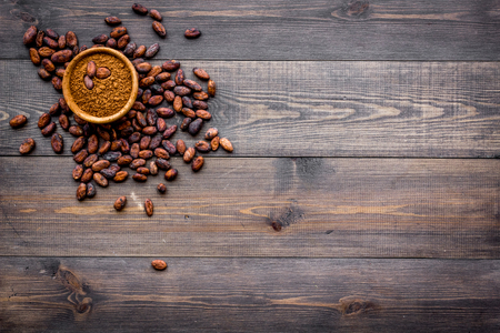 Photo for Main ingredient for chocolate. Cocoa powder in bowl near cocoa beans on dark wooden background top view copy space - Royalty Free Image