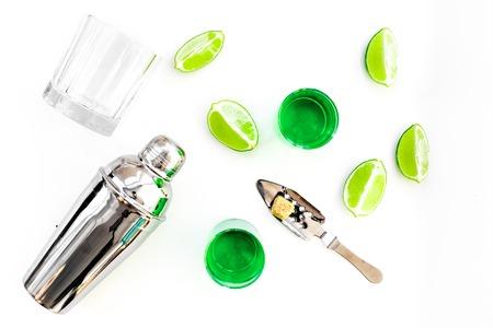 Foto de Make cocktail with absinthe. Shaker, shots, lime slices on white background top view - Imagen libre de derechos
